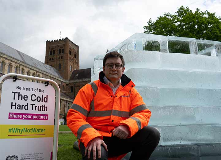 Jake Rigg standing outside St.Albans Cathedral besides the #WhyNotWater Cold Hard Truth art installation.