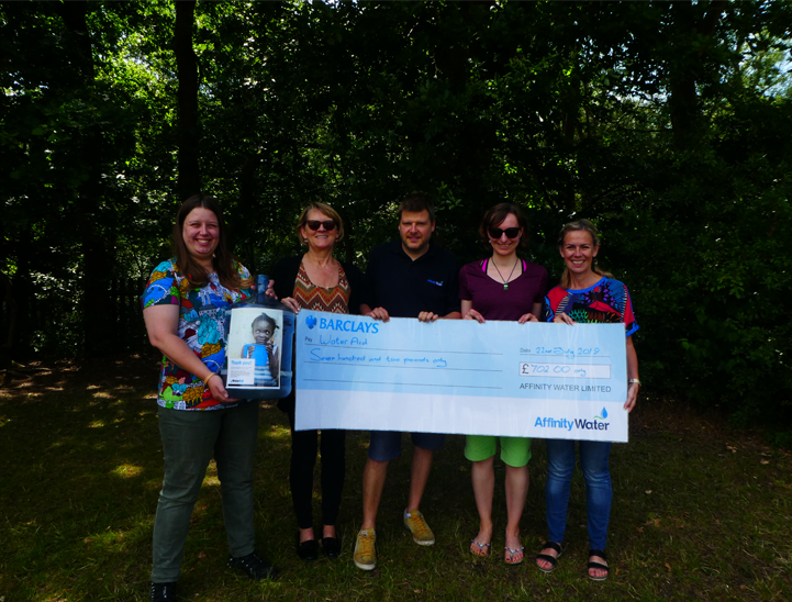 The education team holding the WaterAid cheque.